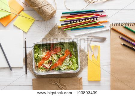 Healthy lunch of artist. Diet concept. Take away food in foil boxes, papers and pencils on working table of creative person or art student. Salmon salad, top view on white wood