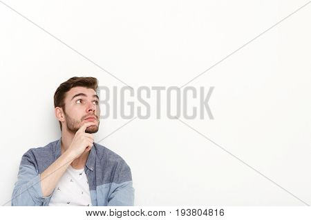 Thoughtful man dreaming, looking away. Young guy with pensive face lost in thoughts, isolated on white studio background
