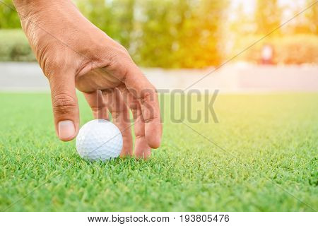 man is taking golfball on green grass