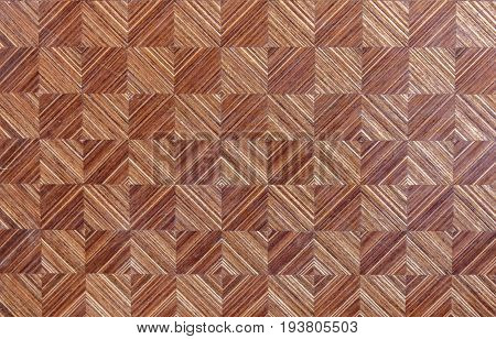 Brown wooden board with geometric mosaic of squares.