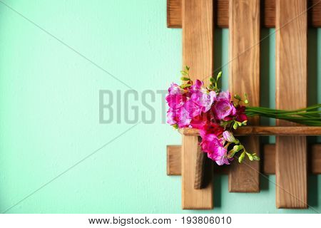 Bunch of beautiful freesia flowers on wooden shelf