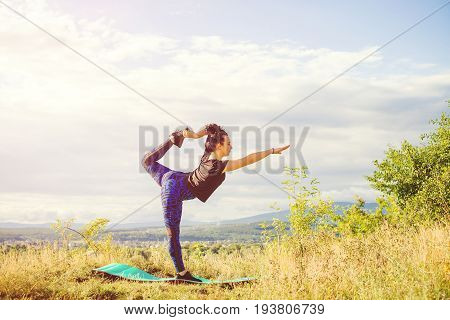 Young Woman Doing Yoga Or Fitness Exercise Outdoor, Nature Landscape At Sunset.