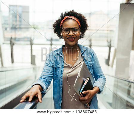 Smiling Young African Entrepreneur Riding An Escalator In An Off