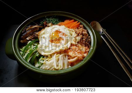 bibimbap, traditional korean food ,mixed rice served in a bowl rice topping alot kind of vegetable ,meat or pork, and fried egg