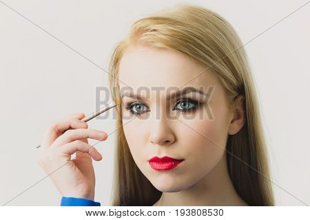 Model applying eye shadow with makeup brush. Adorable girl with red lips and bright make up on cute face with healthy young skin isolated on white. Fashionable woman. Fashion. Visage and cosmetics
