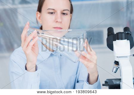 student girl with glass empty Conical flask in hand