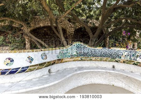 Antonio Gaudi design bench in Park Güell with trees vegetation arches