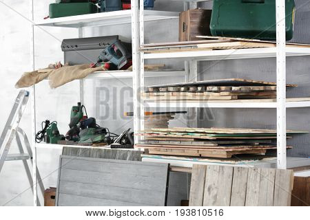Shelves with electric tools in carpenter's workshop