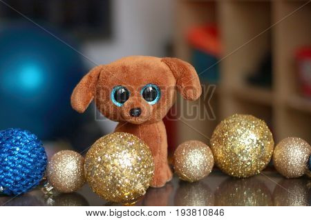 A very sad puppy with Golden and blue Christmas balls in the nursery. Toy. Happy new year and merry Christmas!