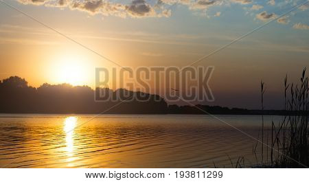 Sunset sky above the forest river. Afterglow nature background