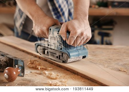 Carpenter working with electric sander in shop poster