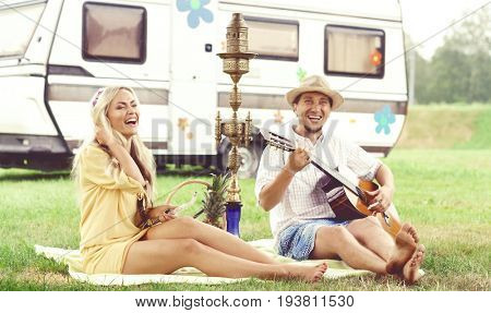 Happy, smiling hippie friends having a picnic outdoors at summer. Trip, holiday, vacation concept.