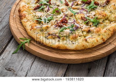 pizza with sun-dried tomatoes, prosciutto, arugula and parmesan cheese on a plate on the table