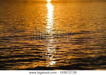 Water surface reflecting sun setting. Rippled water texture. Aquatic background