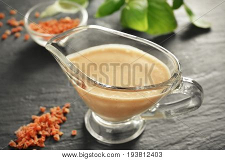 Tasty turkey gravy in sauceboat on table
