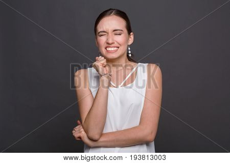 Young woman grimacing her face portrait, dark background. Painful injection, make a wish, powerful emotions concept