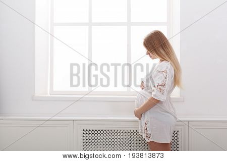 Pregnant woman caressing her belly at home. Young expectant blonde in white dress feeling her baby push, standing at window, copy space. Pregnancy, rest, life, expectation concept
