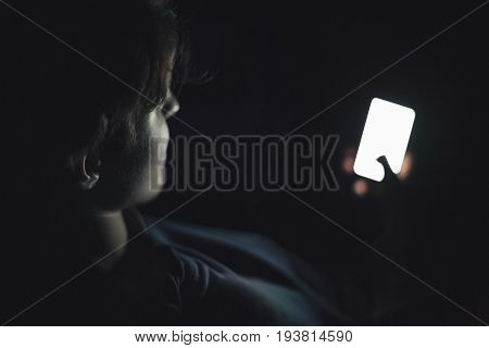 Teenage boy using smart phone in the dark