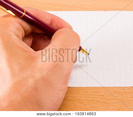 The hand holds the writing pen over the blank sheet intending to write something
