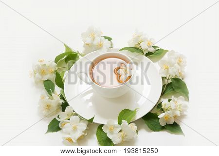 Jasmine flowers around cup of green tea on white background. Top view and concept. Teatime.