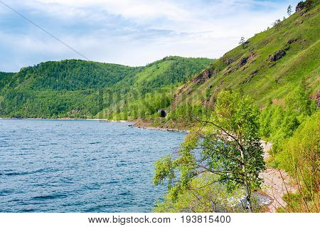 The shore of Lake Baikal and one of the many tunnels is a gallery 83 meters long, built in 1904 on the Circum-Baikal Railway. Siberia, Russia