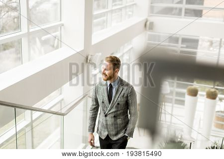 View at young redhair businessman on stairs