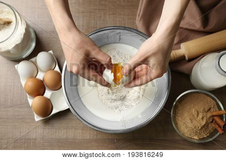 Woman making dough for cinnamon rolls in kitchen