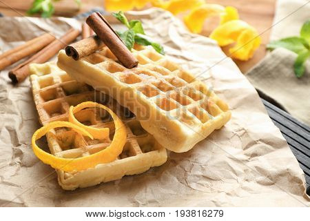 Delicious cinnamon waffles with orange zest on table