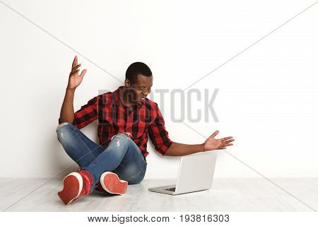 Work done. Happy black man with laptop. Freelancer succeeds in business, at white studio background with crossed legs