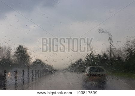 View through the rain-drenched windshield. Blurred silhouette of vehicle