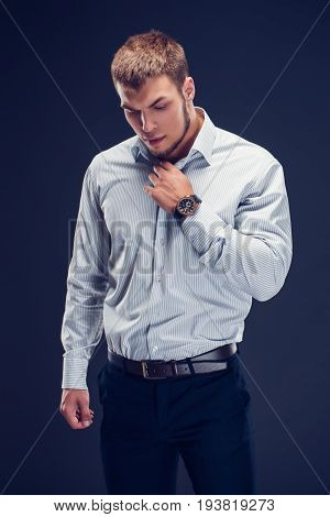 Fashion young beautiful, sexy, sporty guy in a white striped classic shirt button up his collar and looking down on dark background