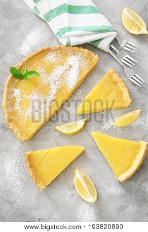 Composition of sliced lemon pie with flatware on table