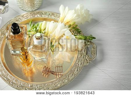 Golden tray with perfume bottles on white table
