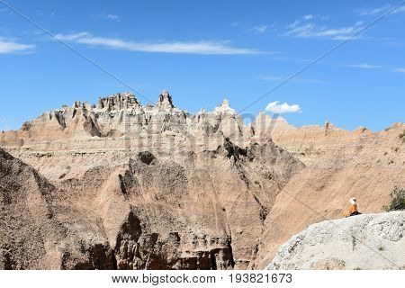 BADLANDS NATIONAL PARK, SOUTH DAKOTA - JUNE 22, 2017: Unidentified woman meditating outdoors facing the harsh landscape of Badlands National Park.