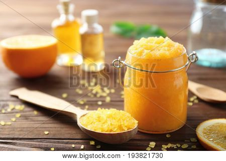 Glass jar with scrub, spoon and sea salt on wooden background