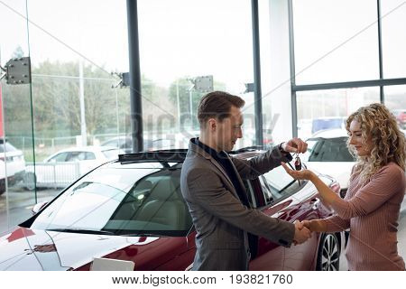 Salesman doing handshake while giving keys to customer while standing in showroom