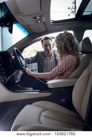 Smiling salesman talking to female customer sitting in car at showroom