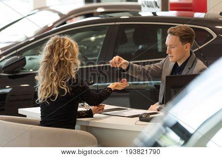 Salesman giving keys to female customer while sitting at desk in car showroom