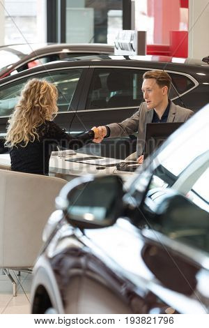 Salesman doing handshake with female customer while sitting desk in car showroom