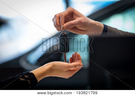 Cropped image of salesman giving car key to customer in showroom