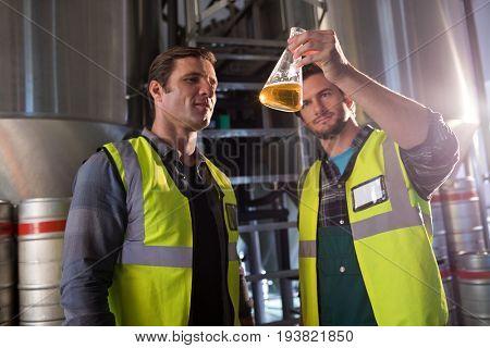 Coworkers examining beer in beaker at brewery