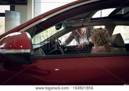 Salesman assisting female customer sitting in car at showroom