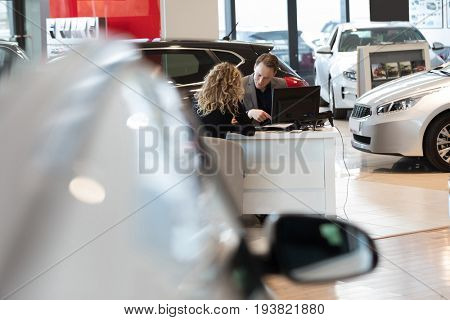 Salesman discussing with female customer while sitting in car showroom
