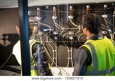 Workers examining pressure gauge at brewery