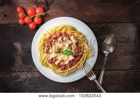 Overhead photo of a plate pf bolognese pasta with grated parmesan cheese and fresh basil leaves, with a fork and a spoon, and a bunch of cherry tomatoes, on a dark rustic texture with a place for text