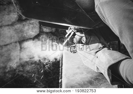 a welder puts the seam on the metal electro arc welding black and white photography