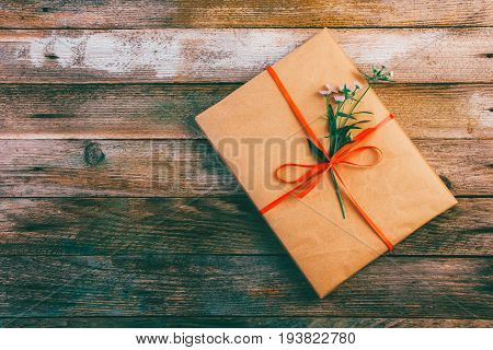Gift in wrapping paper tied with red ribbon and daisy flower on wooden retro grunge background with space for text top view close-up