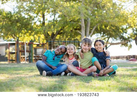 Portrait of happy children with arms around sitting on grassy field at park