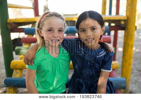 Portrait of friends with arms around sitting on jungle gym at playground