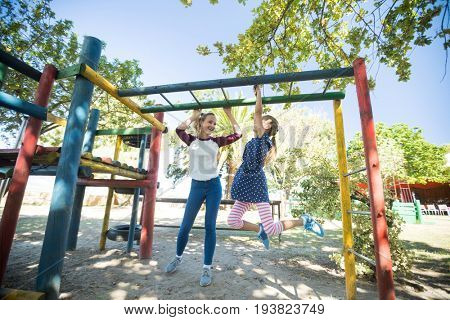 Happy mother talking to daughter hanging on jungle gym at playground